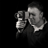 man filming with old classic 8mm cine film camera