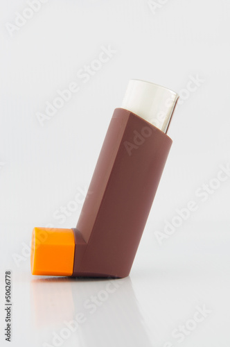 Brown asthma inhaler on white background
