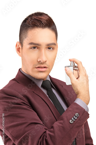 A portrait of a handsome male in black suit using perfume