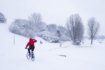 Cyclist in winter park with snow
