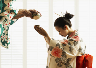 Man pouring woman in kimono tea