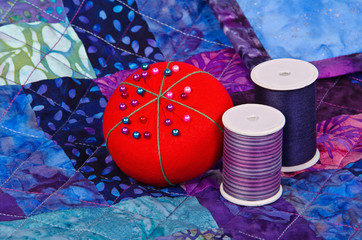 Quilt pattern with quilting thread and pincushion