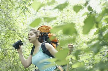 Young female hiker using binoculars