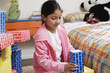 Girl playing with cardboard building blocks
