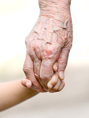 A small kid holding hands of an old woman