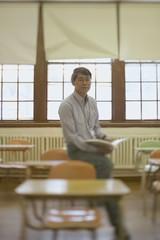 Male teacher sitting in classroom