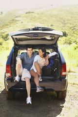 Couple posing inside SUV hatch