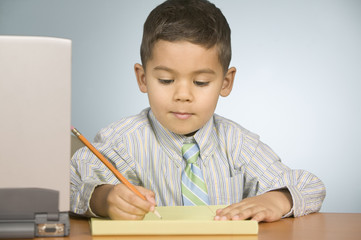 Boy writing on notepad with a pencil