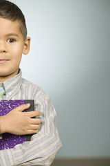 Boy holding a notebook close to his chest