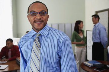 Young businessman with coworkers in background