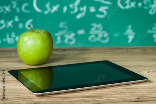 Digital tablet and apple on the desk