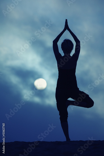 Woman in yoga Tree pose, full moon night