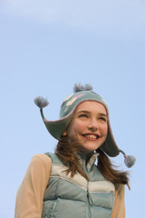 Young girl wearing hat and vest outdoors