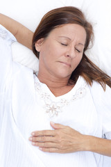 Happy mature woman asleep in bed
