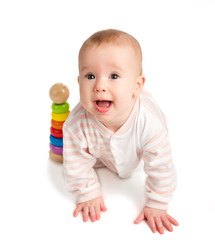 Happy baby playing with a toy pyramid isolated