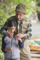 Hispanic grandfather helping granddaughter with fishing pole