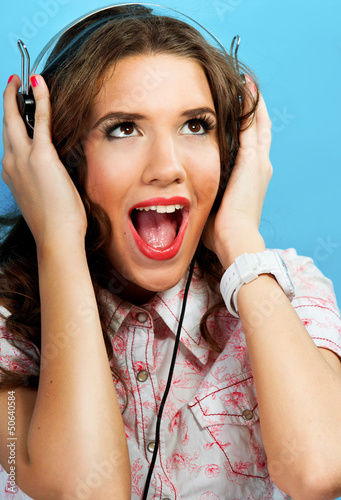 Woman with earphones singing, blue background