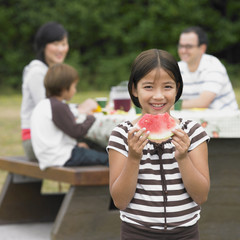 Portrait of Mixed Race girl eating watermelon