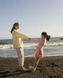 Hispanic grandmother and granddaughter playing at beach