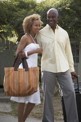 Portrait of African couple carrying luggage