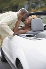 African man kissing wife in car