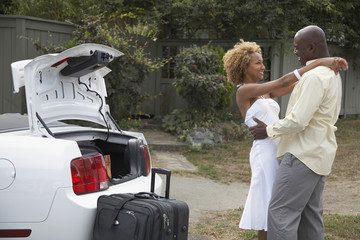 African couple hugging next to luggage