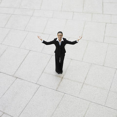 Hispanic businesswoman with arms outstretched