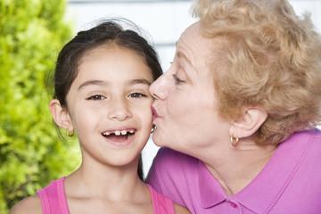 Hispanic grandmother kissing granddaughter on cheek