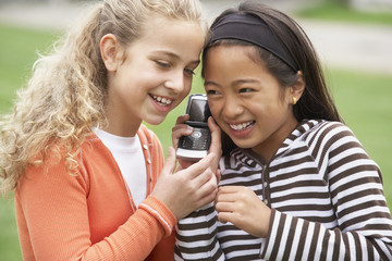 Multi-ethnic girls listening to cell phone
