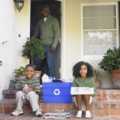 African American father smiling at children with recycling