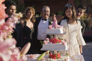 Hispanic girl cutting cake at Quinceanera