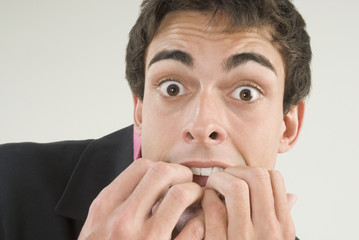 Businessman with fingers in mouth