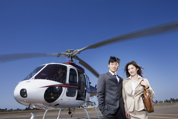 Asian businesspeople next to helicopter