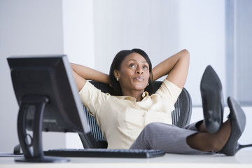 African American businesswoman with feet on desk