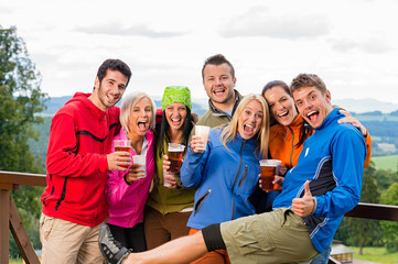 Posing smiling young people with beer outdoors