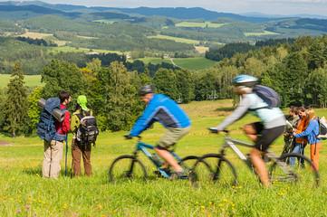 People hiking, riding bicycles on springtime weekend