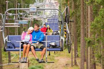 Carefree couple traveling by chair lift wood