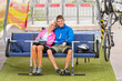 Cuddling couple sitting chair lift with bicycles