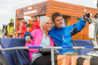 Cheerful couple sitting chair lift man pointing
