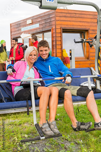 Smiling couple sitting and waiting on chair-lift