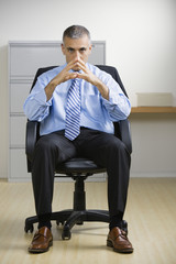 Middle Eastern businessman sitting in chair