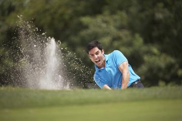 Hispanic man playing golf in sand trap