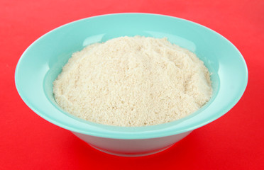 Powdered milk in bowl for baby on red background