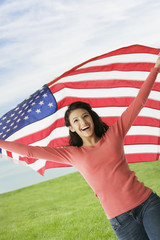 Hispanic teenaged girl holding American flag