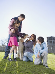 Multi-ethnic family with dog in park