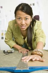Asian female fashion designer using t-square