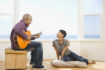 African man playing guitar for wife