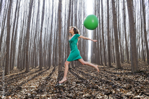 Beautiful blonde girl, dressed in green, jumping into the woods