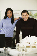 Multi-ethnic architects next to house model
