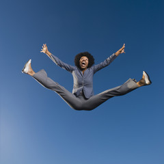 African businesswoman jumping in mid-air